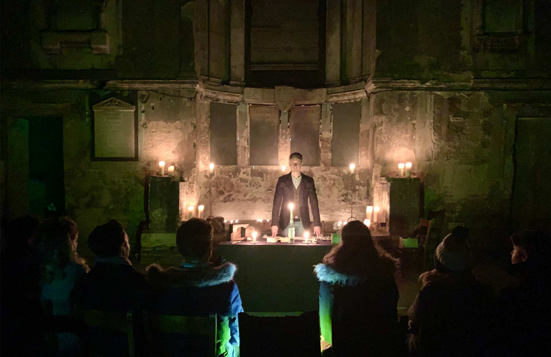 Christopher Howell stands in a derelict church at a table in candlelight