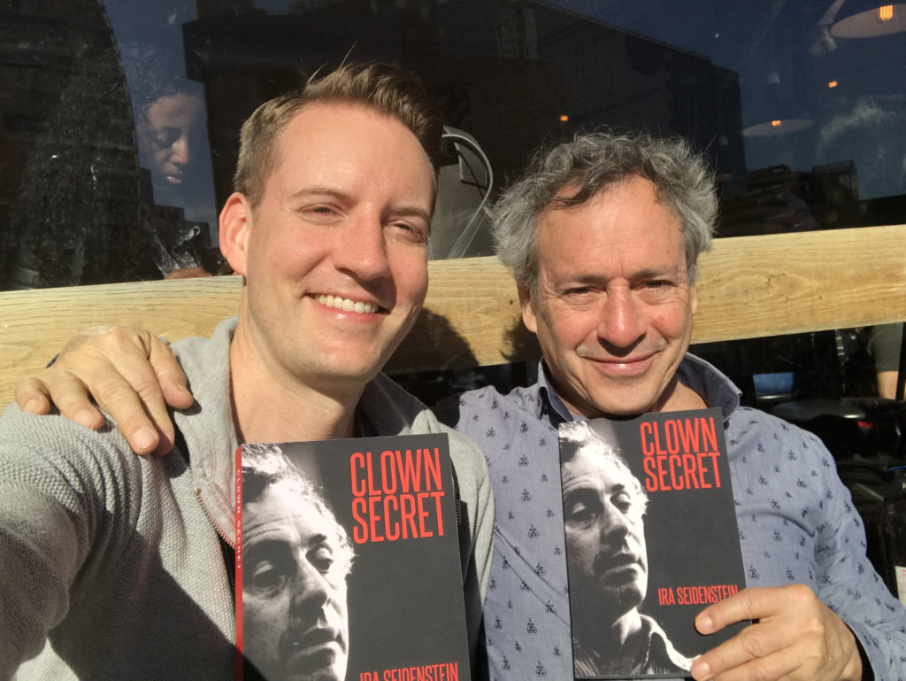 Christopher Howell sits with Ira Seidenstein as they hold new copies of his book Clown Secret first published in 2018.