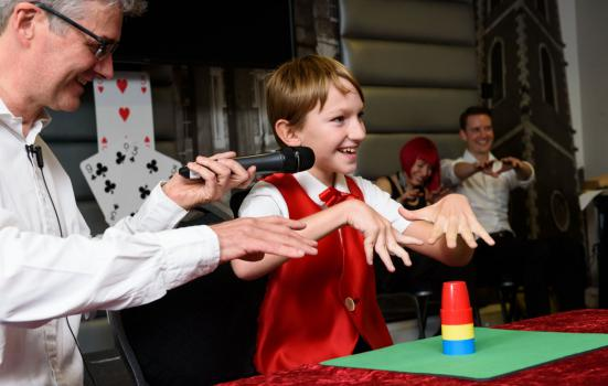 Young magician performs at a magic show.