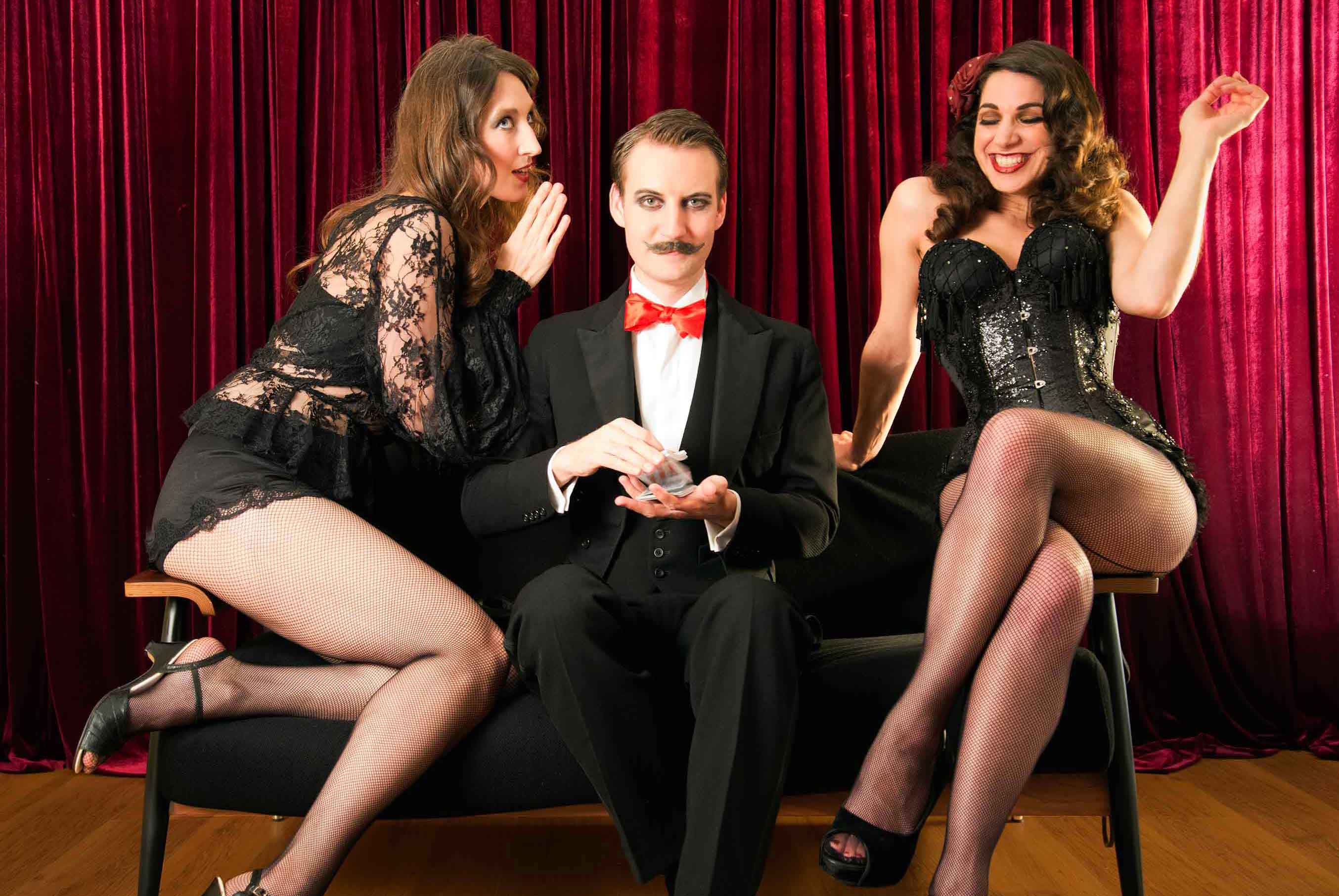 Close-up magician Norvil and the Vedettes gossip on the sofa.