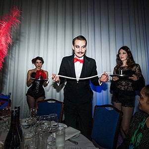 Party magician Norvil performs holding a rope at a table.