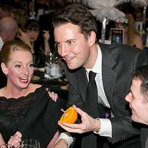 Party magician Christopher Howell holds an orange while two guests watch laughing.