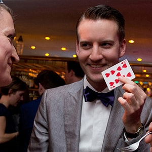 London wedding magician reveals a card to audience.