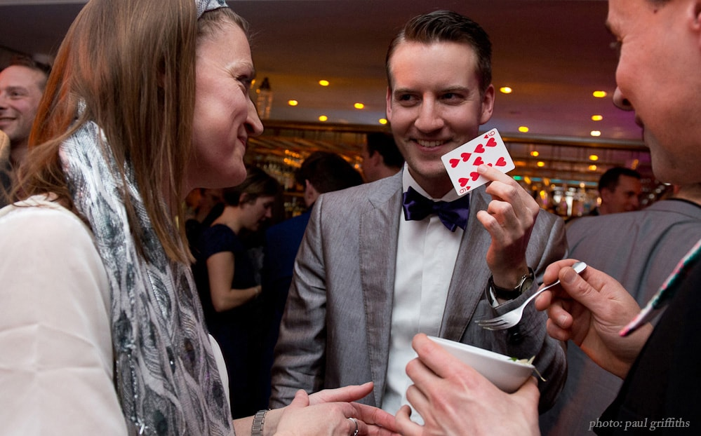 Party magician Christopher Howell stands in a bow tie holding a card while two guests watch smiling.