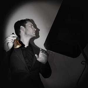 Magician Christopher Howell holds a bell and looks ialnto the darkness in his Seance magic show.