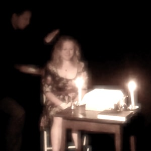 Lady from audience closes eyes sat next to candle waiting for a ghost in magician Christopher Howell's Seance magic show.