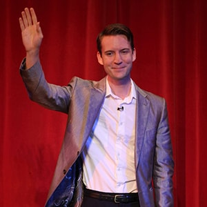American magician in London Christopher Howell waves to the audience during his Parlour magic show.