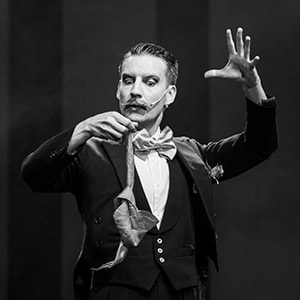 Stage magician Norvil holds a handkerchief in his show for hire.