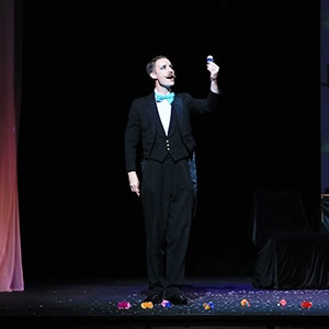 Greatest showman party magician Norvil holds up a flower.
