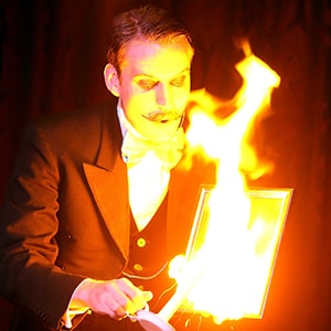 Stage magician hire performs with fire on stage.