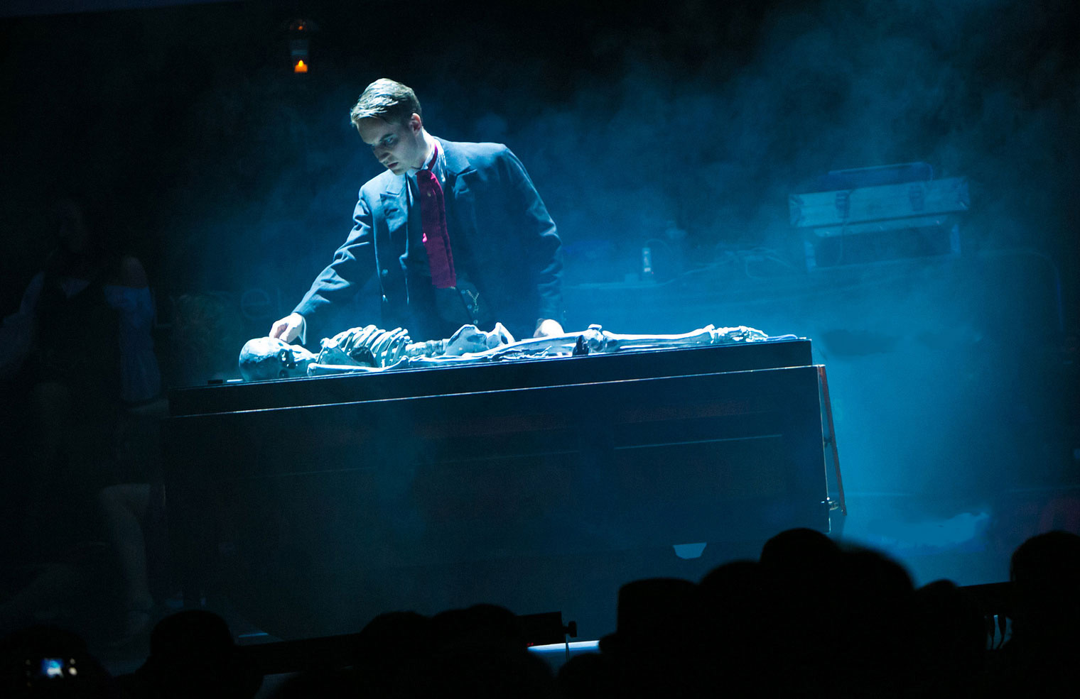 Magic consultant Christopher Howell looks down at a smokey skeleton on stage in his Jack the Ripper act.