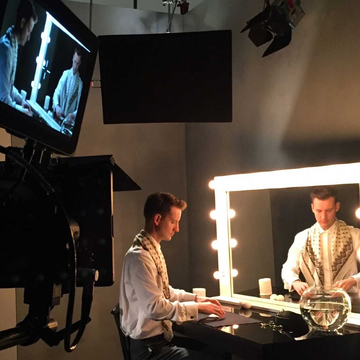 Thumbnail of magician Christopher Howell practicing in front of a dressing room mirror on set for the Canali commercial.