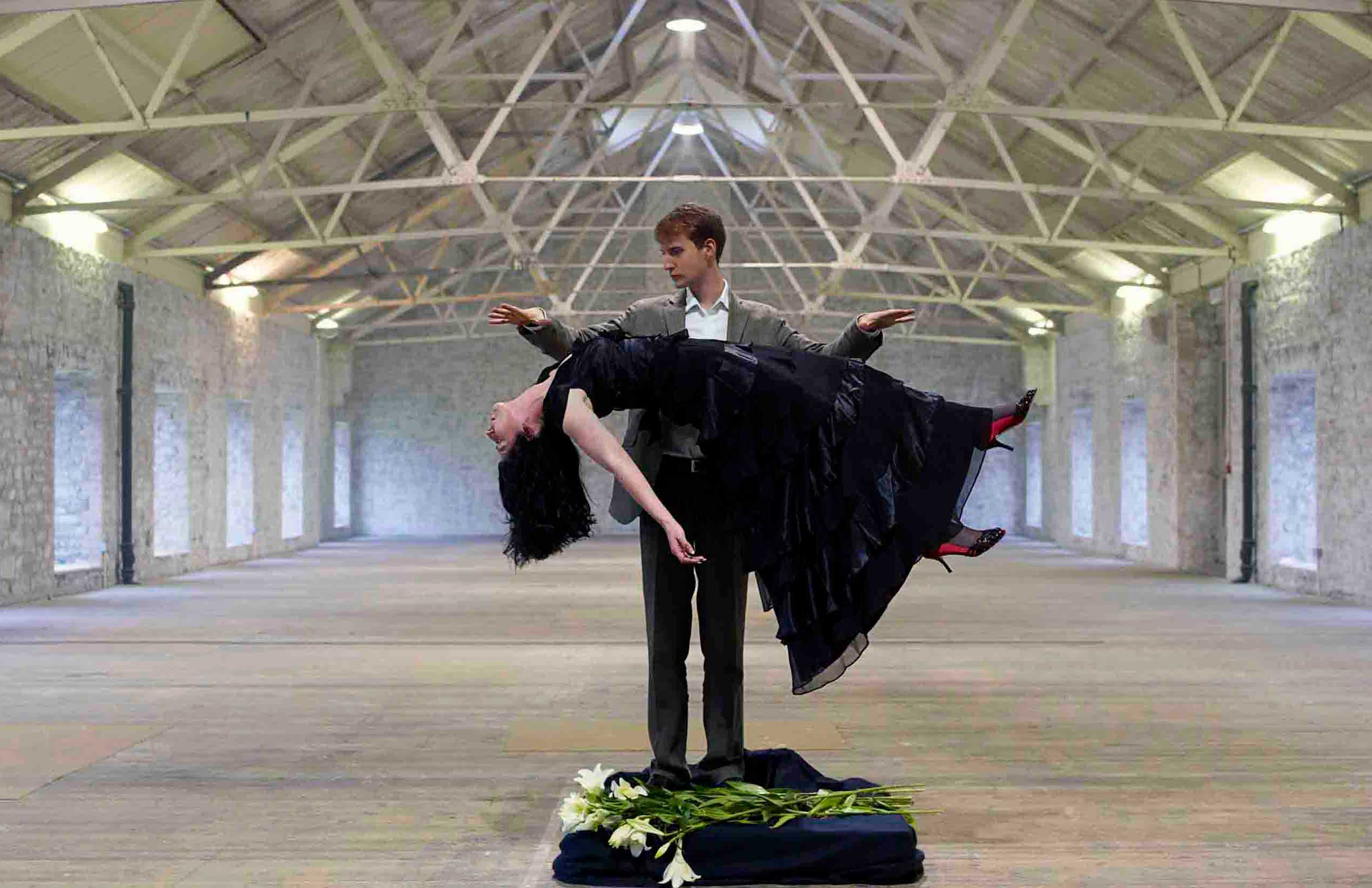 A thumbnail of artist Francesca Steele levitating lillies in an empty warehouse in front of magician Christopher Howell.