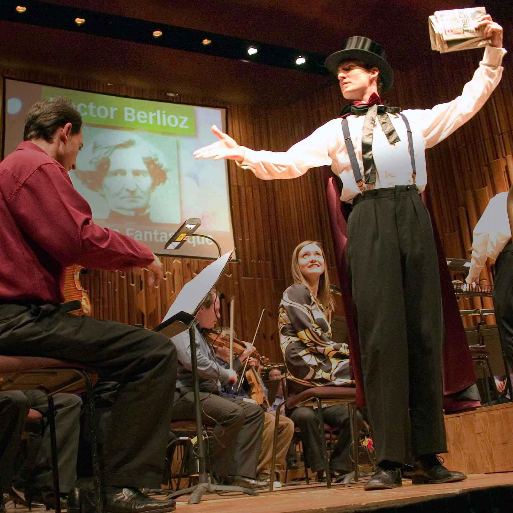 Thumbnail of magician Christopher Howell in a top hat holding a newspaper on stage with the LSO at The Barbican.