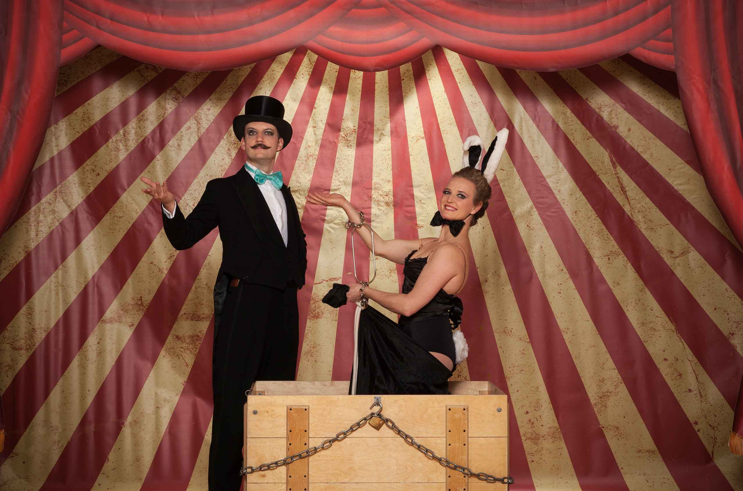 Cabaret magician double act stand on stage in vintage costume.