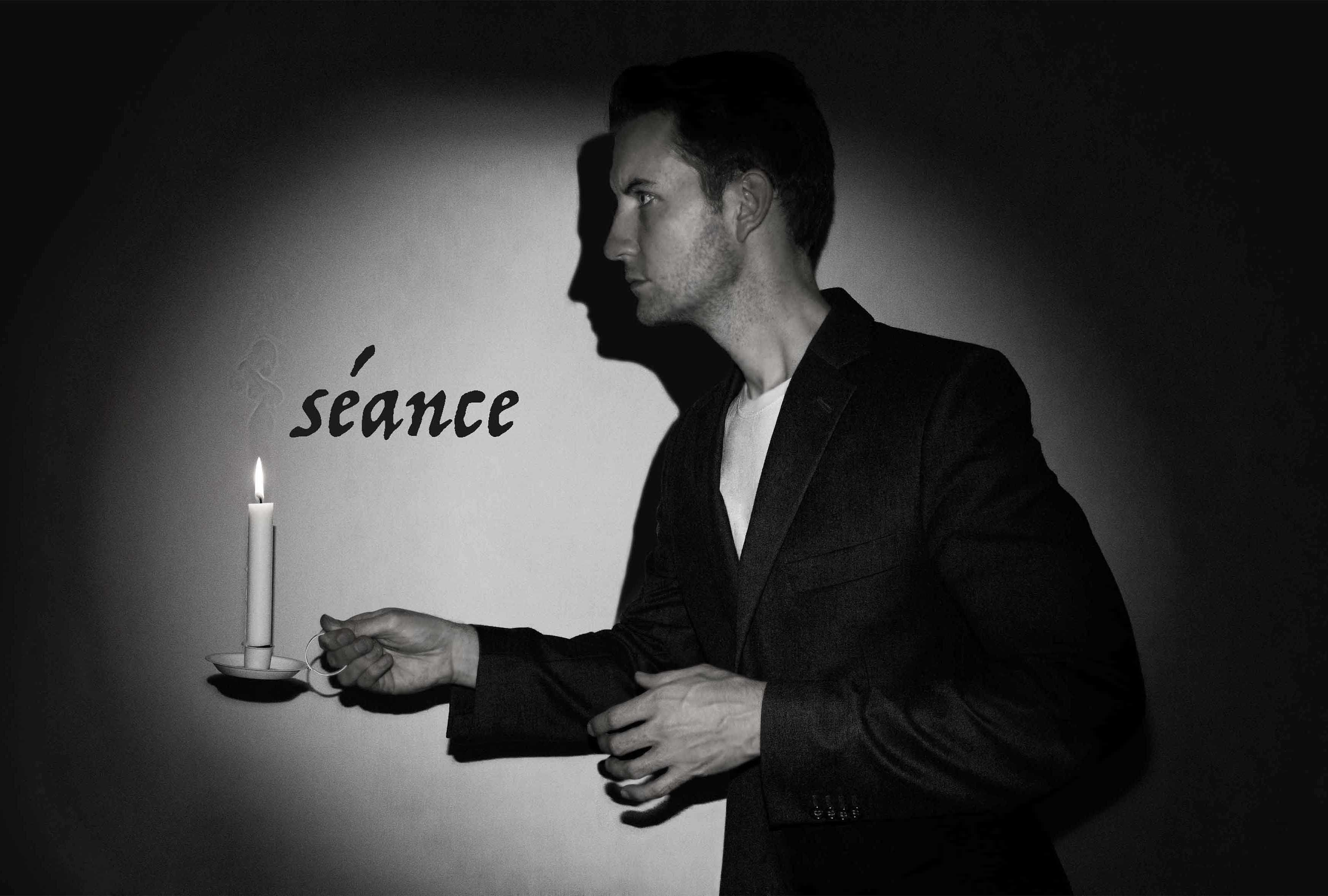Spooky seance magic show with Christopher Howell holding the candle.