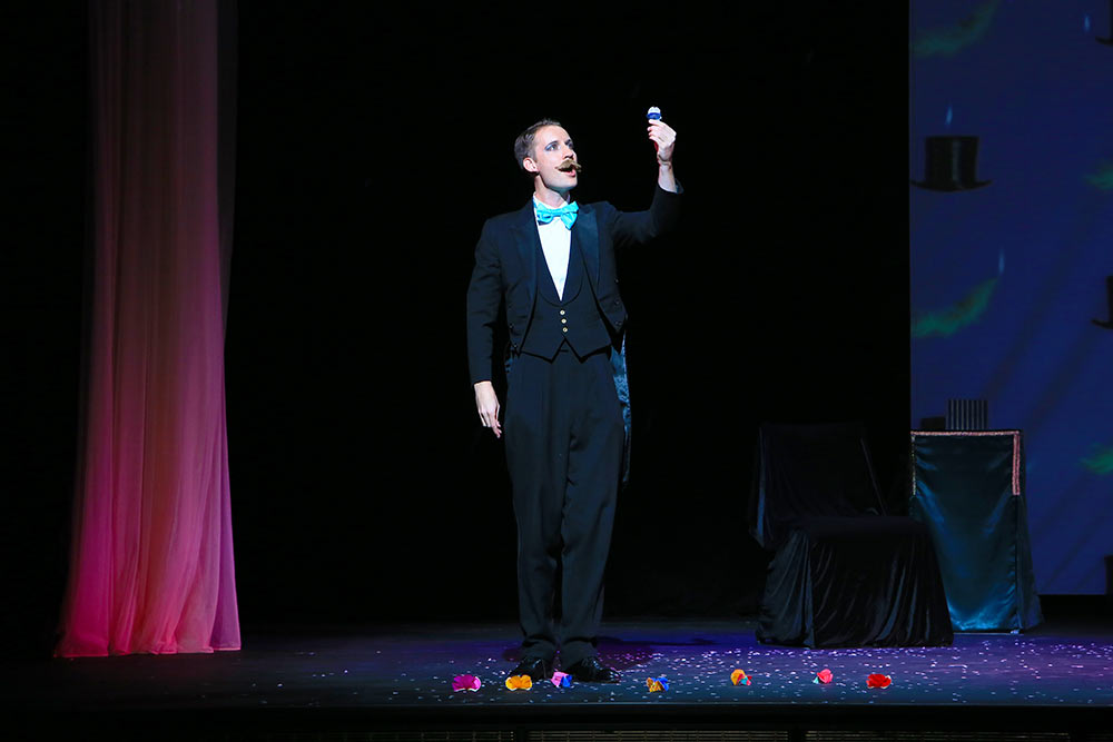 Magician who can sing stands on stage in a serenade.
