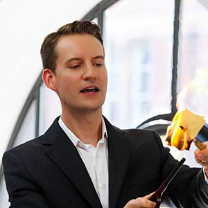 American magician in London Christopher Howell burns an envelope during his Parlour magic show.