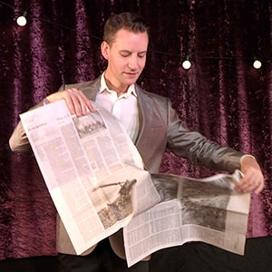 American magician in London Christopher Howell tears a newspaper on stage in his Parlour magic show.