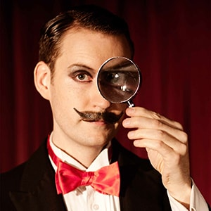 Stage magician hire Norvil looks through magnifying glass.